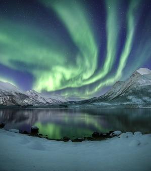 Tiro vertical das montanhas cobertas de neve sob as belas luzes do norte no céu