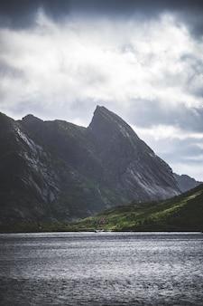 Tiro vertical das montanhas e um lago nas ilhas lofoten