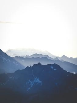 Tiro vertical das montanhas sob um céu brilhante