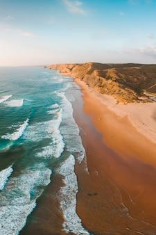 Tiro vertical das ondas do mar de tirar o fôlego e da praia com falésia rochosa sob o céu azul