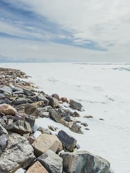Tiro vertical das pedras perto do vale coberto de neve no inverno sob o céu nublado