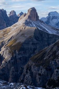 Tiro vertical das rochas cobertas de neve nos alpes italianos