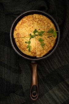 Tiro vertical de alto ângulo closeup de uma omelete dividido em quatro pedaços em um torrador