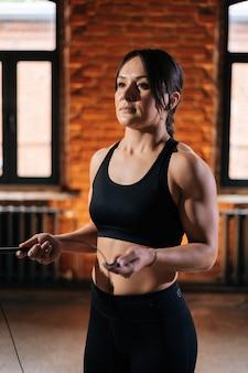 Tiro vertical de aptidão atlética jovem com corpo forte e bonito em roupas esportivas pretas, segurando a corda de pular durante o treinamento de treino. treino muscular caucasiano feminino no ginásio escuro.