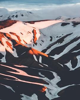 Tiro vertical de belas montanhas nevadas na zona rural da islândia ao pôr do sol