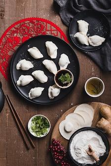 Tiro vertical de bolinhos chineses tradicionais em um prato e os pauzinhos em uma mesa de madeira