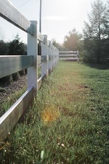 Tiro vertical de cercas de madeira cinza em um campo de grama durante o dia