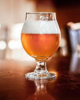 Tiro vertical de cerveja em um copo de vidro com um fundo desfocado