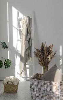 Tiro vertical de cestas de vime com flores e plantas inoor com cobertor na escada de madeira