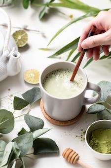 Tiro vertical de chá verde com leite com leite em um copo branco com folhas verdes e colher de pau