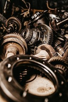 Tiro vertical de cinza, engrenagens metálicas e peças de automóvel