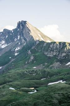 Tiro vertical de colinas gramadas perto de uma montanha com um céu claro ao fundo