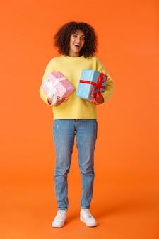 Tiro vertical de corpo inteiro animado bonito feliz fêmea afro-americana recebeu presentes para festas, de pé divertido e encantado, segurando dois presentes embrulhados, laranja