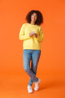 Tiro vertical de corpo inteiro pensativo, adorável e sonhadora mulher afro-americana com cabelos cacheados, olhando para cima e sorrindo, imaginando coisas, pensativo, pensando a resposta como segurando smartphone
