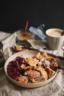 Tiro vertical de deliciosas panquecas fofas com cereja e açúcar de confeiteiro