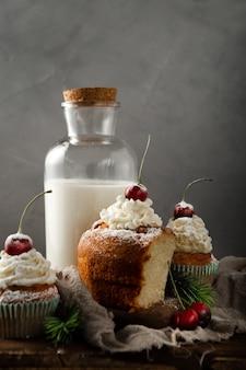 Tiro vertical de deliciosos cupcakes com açúcar de confeiteiro e uma cereja por cima com leite