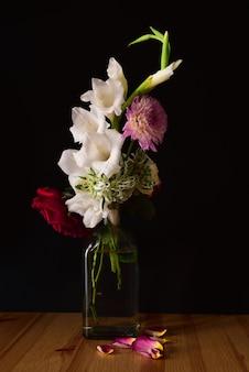 Tiro vertical de diferentes flores em uma jarra em uma superfície de madeira com um fundo preto