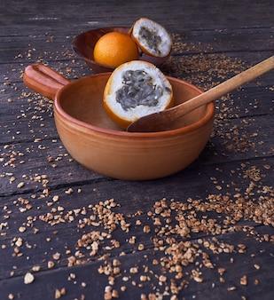 Tiro vertical de dois frutos de granadilha em duas tigelas de madeira diferentes em uma superfície escura