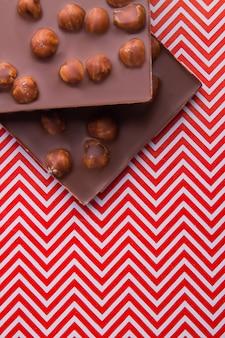 Tiro vertical de dois pedaços de barra de chocolate com avelãs