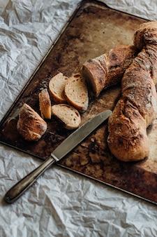 Tiro vertical de fatias de pão baguete em uma tábua