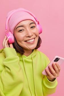 Tiro vertical de feliz jovem asiática vestida com roupas casuais gosta de música favorita usa fones de ouvido com boa qualidade de som mantém smartphone moderno isolado sobre a parede rosa.