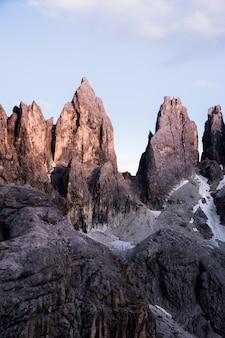 Tiro vertical de grandes rochas no topo de uma montanha com um céu claro no