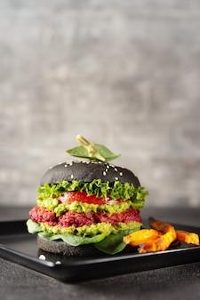 Tiro vertical de hambúrguer vegetariano preto com batata doce frita