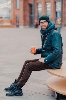 Tiro vertical de homem barbudo bonito vestido com roupas de rua, beber café para ir