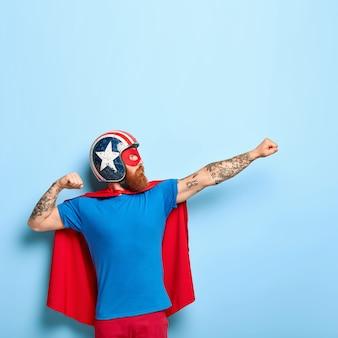Tiro vertical de homem barbudo fazendo gesto de voar, cerrando os punhos, tem objetivo a atingir