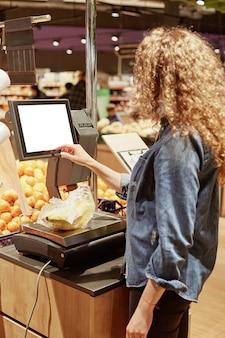 Tiro vertical de jovem pesa bananas em balanças eletrônicas com tela sensível ao toque, compra frutas no supermercado, fica para trás