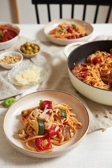 Tiro vertical de macarrão com vegetais e ingredientes em uma mesa branca
