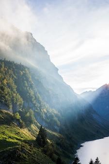 Tiro vertical de montanhas arborizadas perto da água sob um céu nublado durante o dia
