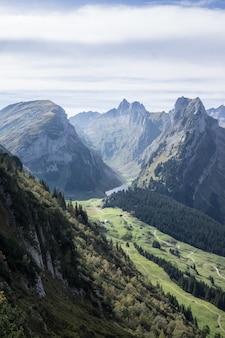 Tiro vertical de montanhas arborizadas sob um céu nublado durante o dia
