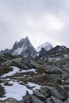 Tiro vertical de montanhas nevadas com um céu nublado