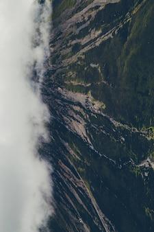 Tiro vertical de montanhas verdes cobertas por nuvens brancas