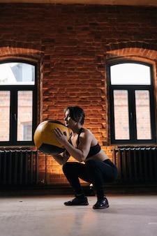Tiro vertical de mulher atlética jovem musculosa com corpo forte, vestindo roupas esportivas, fazendo agachamentos com medicine ball durante o treinamento de treino. treino feminino de fitness caucasiano fora exercitando-se no ginásio escuro.