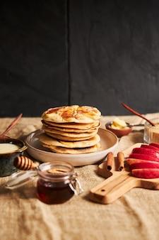 Tiro vertical de panquecas de maçã em um prato com fatias de maçã, mel e ingredientes ao lado