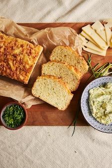 Tiro vertical de pão com queijo e manteiga de ervas em uma madeira