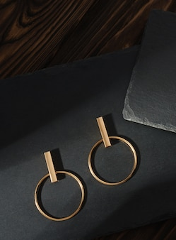 Tiro vertical de par de brincos de ouro modernos em fundo de pedra escuro na superfície de madeira marrom