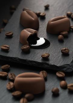 Tiro vertical de pedaço de chocolate picado com grãos de café em placas de pedra escuras
