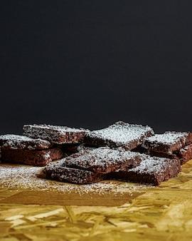 Tiro vertical de pedaços de brownie cobertos com açúcar de confeiteiro em uma superfície de madeira