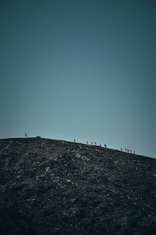 Tiro vertical de pessoas andando em uma colina rochosa íngreme à distância