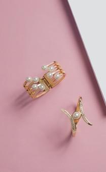 Tiro vertical de pulseiras de ouro e pérolas na superfície rosa e branca