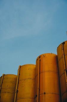 Tiro vertical de quatro silos metálicos amarelos com o céu azul