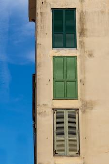 Tiro vertical de um antigo prédio de concreto com janelas resistidas com texturas interessantes