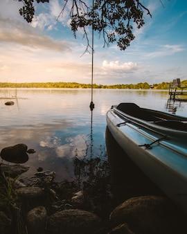 Tiro vertical de um barco em um lago rodeado de plantas e pedras