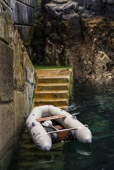 Tiro vertical de um barco no lago perto da escada, cercada por belas formações rochosas