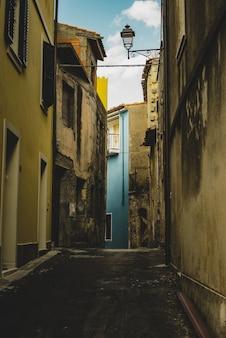 Tiro vertical de um beco vazio alinhado com velhos edifícios amarelos, levando a um prédio azul