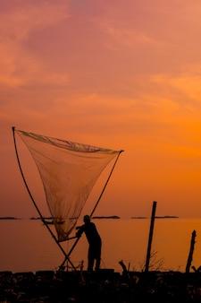 Tiro vertical de um belo pôr do sol sobre o mar com um pescador segurando uma rede