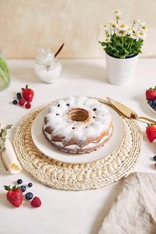 Tiro vertical de um bolo de anel com frutas e pó em uma mesa branca com branco